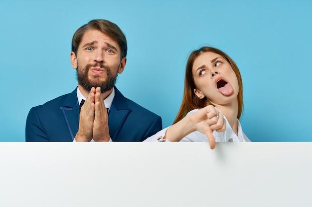Homme et femme avec une affiche publicitaire de maquette blanche fond isolé