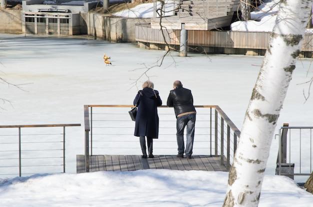 Un homme et une femme d'âge moyen se tiennent sur le pont près de l'étang couvert de glace et admirent les canards.
