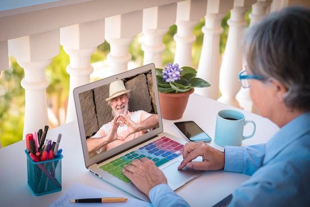 Un homme et une femme âgés sont absents en raison du verrouillage du coronavirus dans le chat vidéo à partir d'un ordinateur portable