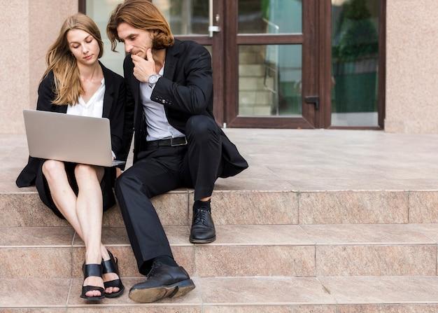Homme et femme à l'aide d'un ordinateur portable dans les escaliers