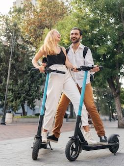Homme et femme à l'aide de scooters à l'extérieur