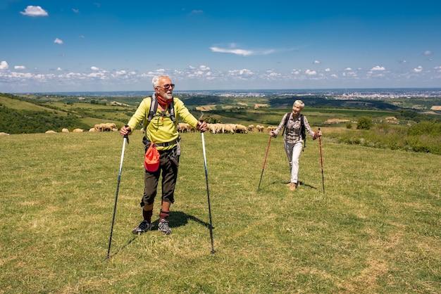 Homme et femme aîné couple randonnée sur une prairie à flanc de montagne
