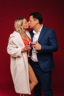 Un homme et une femme amoureuse d'une coupe de champagne sur fond rouge s'embrassent.