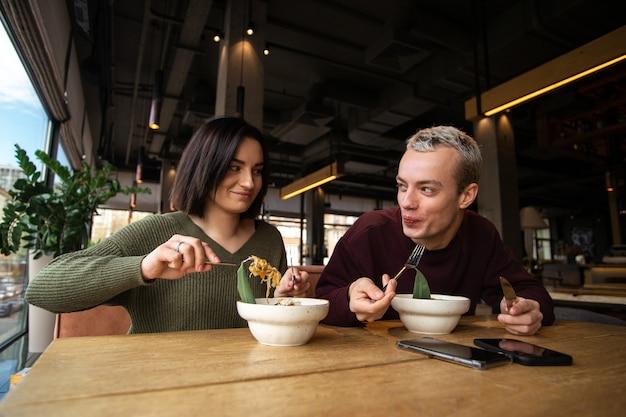 Homme et femme appréciant la nourriture asiatique