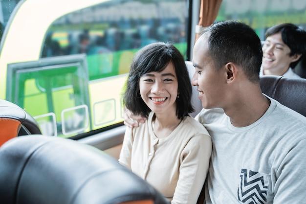 Un homme et une femme asiatique bavardant et riant assis dans le bus en voyageant