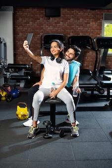 Homme et femme asiatiques indiens sportifs se reposant entre les exercices et utilisant un smartphone au gymnase, présentant quelque chose ou prenant une photo de selfie