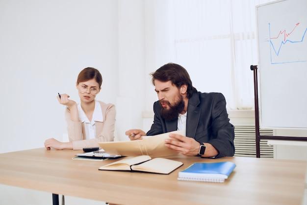 L'homme et la femme assis à un bureau des professionnels de la communication de travail de bureau