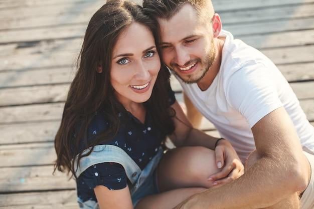 Homme et femme assis sur une jetée en bois