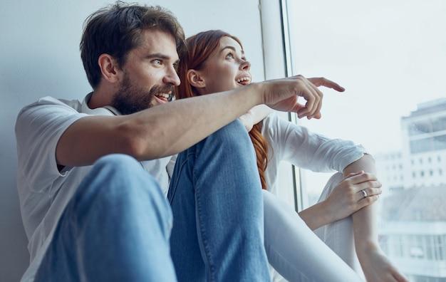 Homme et femme assis sur le rebord de la fenêtre technologie communication fenêtre intérieure joie