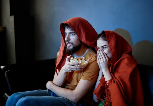 L'homme et une femme assise sur un canapé devant la télévision à l'intérieur