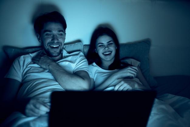 Homme et femme au lit avec un ordinateur portable ouvert regardant un film la nuit