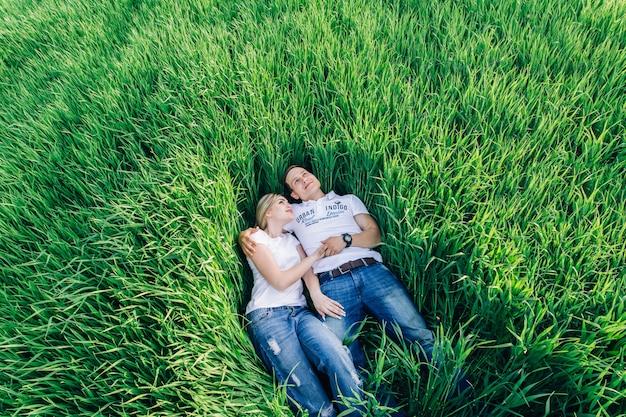 Homme et femme au repos dans un champ vert.
