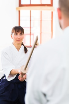 Homme et femme ayant un combat à l'épée d'aïkido
