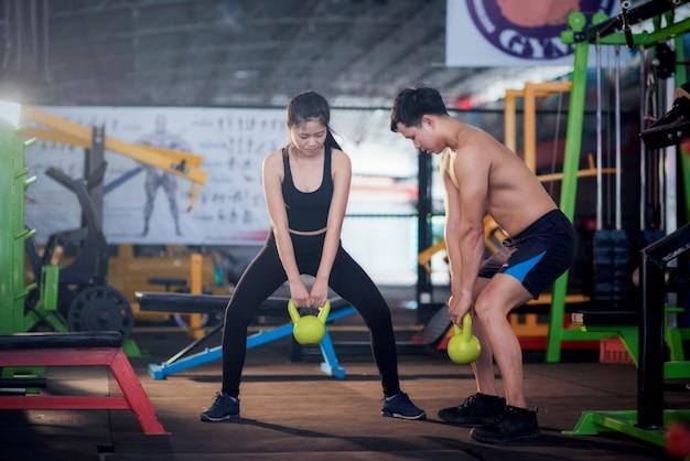Homme et femme ayant un entraînement fonctionnel avec kettlebell