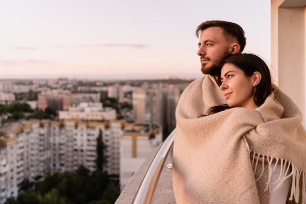 Homme femme, sur, balcon, à, coucher soleil, dans ville