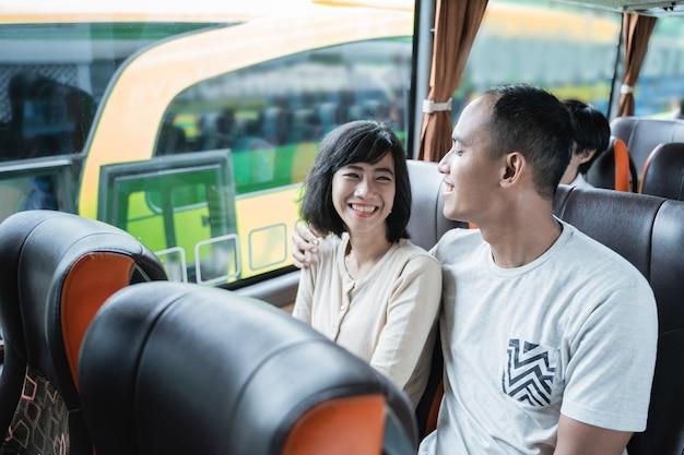 Un homme et une femme bavardant et riant assis dans le bus en voyageant