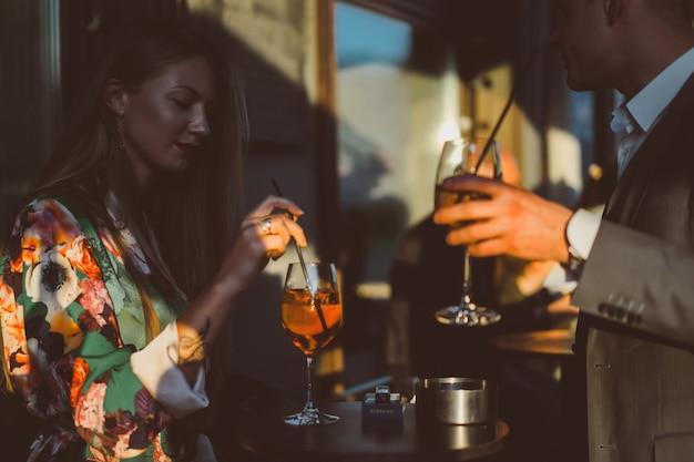 L'homme et la femme boivent des cocktails dans un café de rue sur la terrasse d'été. élégant couple de boissons aperol spritz.