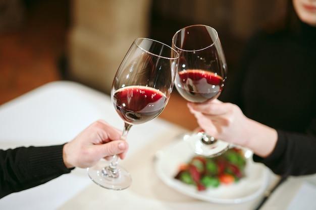 Homme et femme buvant du vin rouge. sur la photo, gros plan des mains avec des lunettes.
