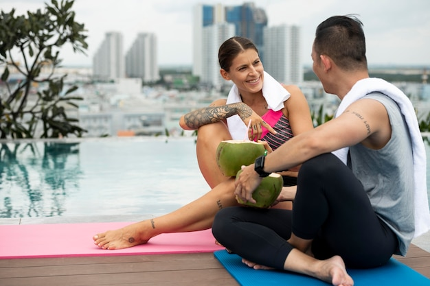 Homme et femme buvant de l'eau de coco après le yoga