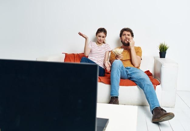 Homme et femme sur canapé avec intérieur de salle de fleurs et écran de télévision