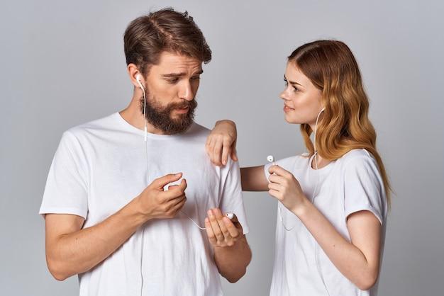Homme et femme avec un casque dans les mains musique fond clair