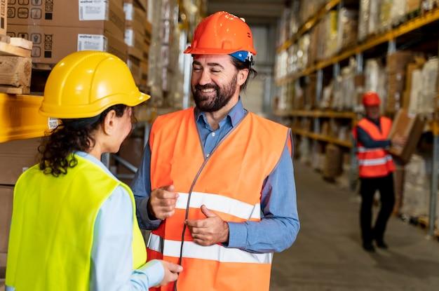 Homme et femme avec casque travaillant dans l'entrepôt