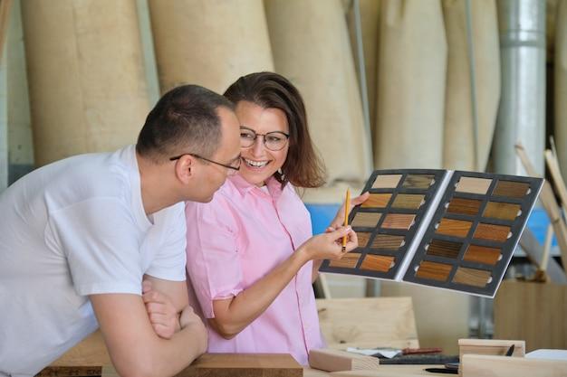 Homme et femme choisissant le traitement de finition des meubles en bois