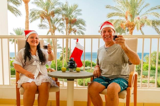 Un homme et une femme coiffés de chapeaux de père noël fêtent noël sur le balcon sur fond de mer. photo horizontale.