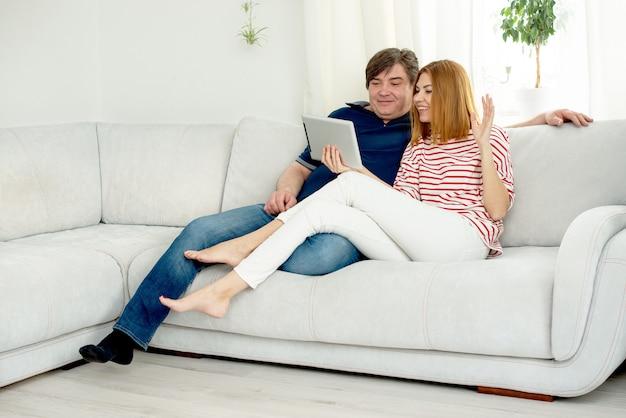 L'homme et la femme communiquent par liaison vidéo. discuter en ligne et agiter l'écran de l'ordinateur.