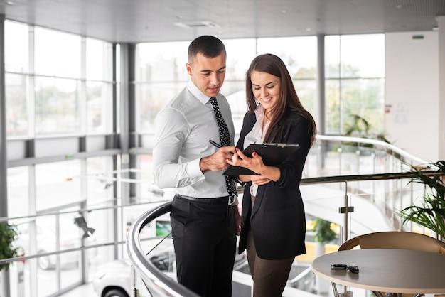 Homme et femme concluant un accord chez un concessionnaire
