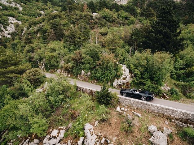 Un homme et une femme conduisent dans une voiture ouverte le long d'un sentier pittoresque dans les montagnes du monténégro