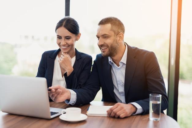 Un homme et une femme en costume d'affaires strict discutent.