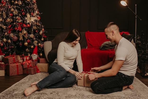 Homme et femme couple amoureux ouvrir les coffrets cadeaux délier un arc près de l'arbre de noël