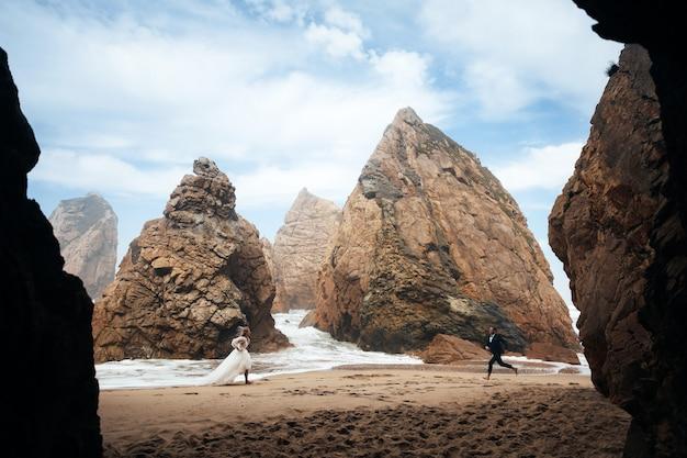 Homme et femme courent l'un sur l'autre sur la plage parmi les rochers