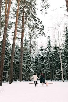 Un homme et une femme courent avec un chien à travers une forêt enneigée