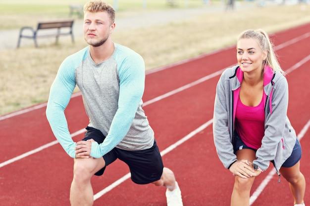 Homme et femme course sur piste extérieure