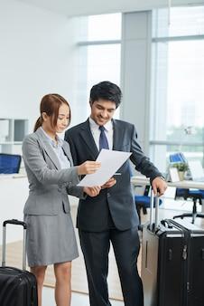 Homme, femme, dans, affaires, costumes, debout, bureau, valises, et, regarder ensemble, à, document