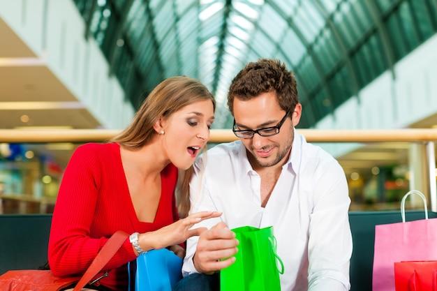 Homme et femme dans un centre commercial avec des sacs
