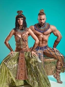 L'homme et la femme dans les images du pharaon égyptien et de cléopâtre sur fond bleu studio