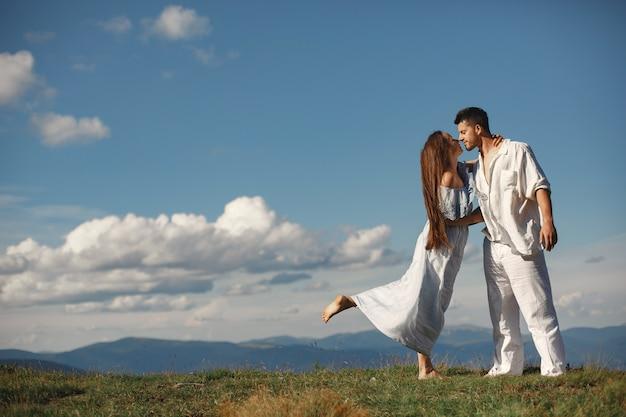 Homme et femme dans les montagnes. jeune couple amoureux au coucher du soleil. femme en robe bleue. peopel debout sur un fond de ciel.