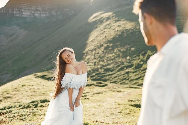 Homme et femme dans les montagnes. jeune couple amoureux au coucher du soleil. femme en robe bleue.