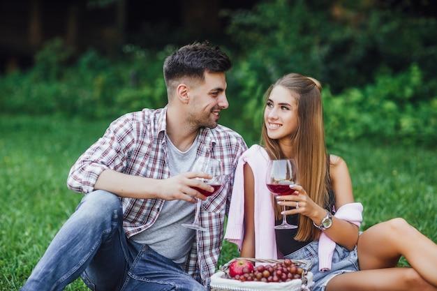 Homme et femme dans le parc avec du vin rouge