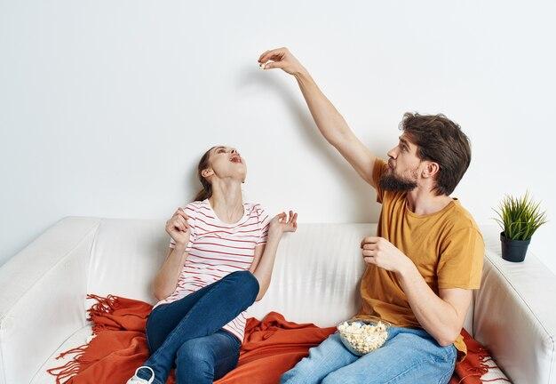 Un homme et une femme dans une pièce lumineuse s'asseoir sur le canapé avec du pop-corn