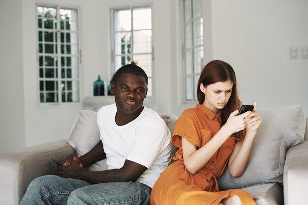 Homme et femme dans le salon sur le canapé à discuter