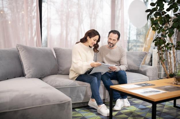 Homme et femme dans un salon de meubles assis sur un canapé confortable