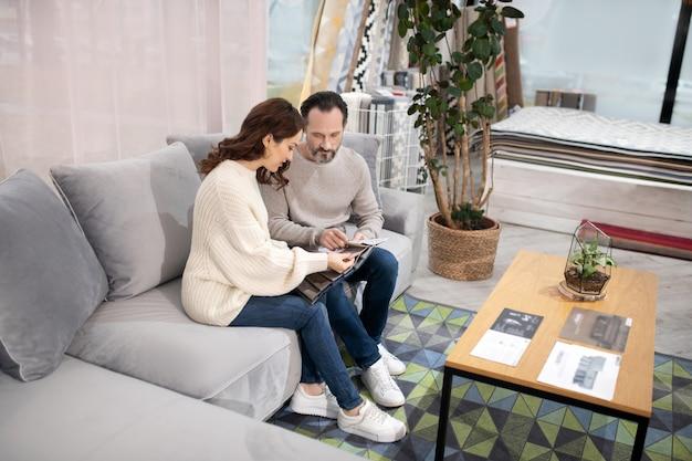 Homme et femme dans un salon de meubles en choisissant des détails de meubles