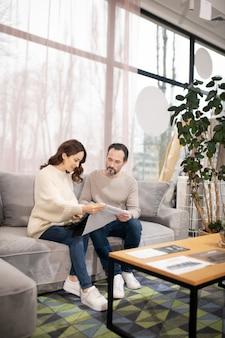 Homme et femme dans un salon de meubles en choisissant le tissu pour canapé