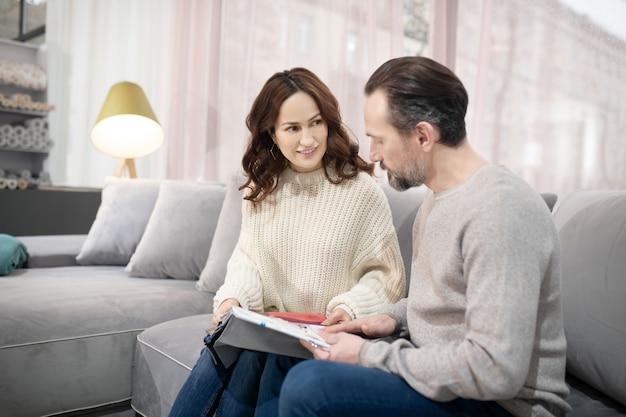 Homme et femme dans un salon de meubles discutant des modèles