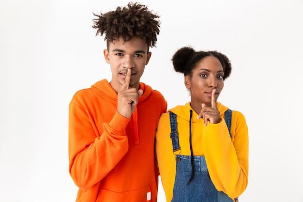 Homme et femme dans des vêtements colorés tenant les doigts à la bouche, isolé sur mur blanc