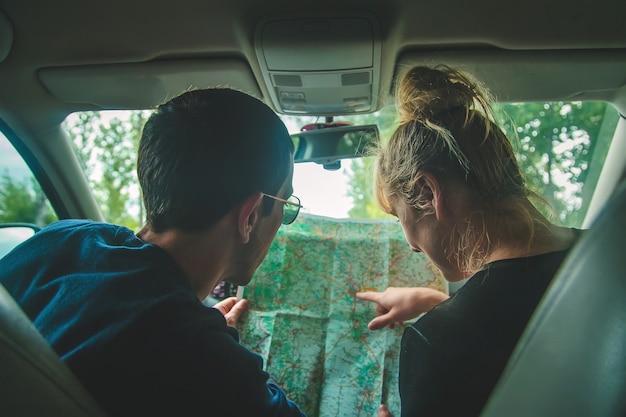 Un homme et une femme dans la voiture regarde la carte